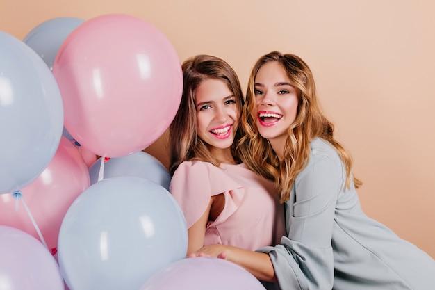 パーティーで彼女の友人を抱きしめる巻き毛の女性を笑う