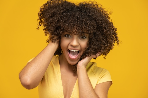 Laughing curly woman in sweater touching her hair
