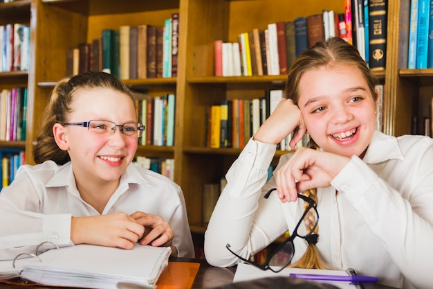 Laughing cute girls sitting with copybooks