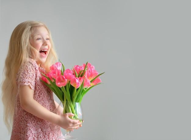 회색 바탕에 핑크 튤립 꽃병을 들고 귀여운 금발 소녀를 웃 고