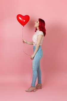 빨간 머리와 청바지를 가진 웃음, 기쁘게 여자는 그녀의 손에 비행 빨간 풍선을 본다
