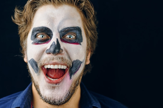 Laughing, disheveled hair, close-up portrait. make-up man of the day of death on halloween. copy space