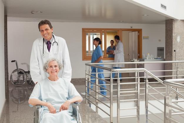 Смеющийся доктор, подталкивающий кресло-коляску
