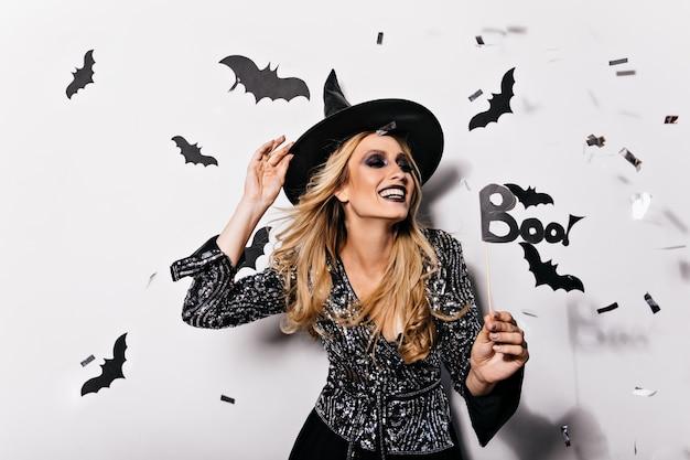 박쥐와 함께 포즈 마녀 모자에 황홀한 여자를 웃 고있다. 할로윈을 축하하는 좋은 기분 금발 소녀의 실내 사진.
