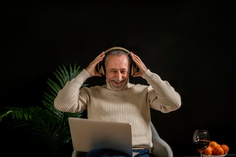 Laughing elderly male putting on headphones