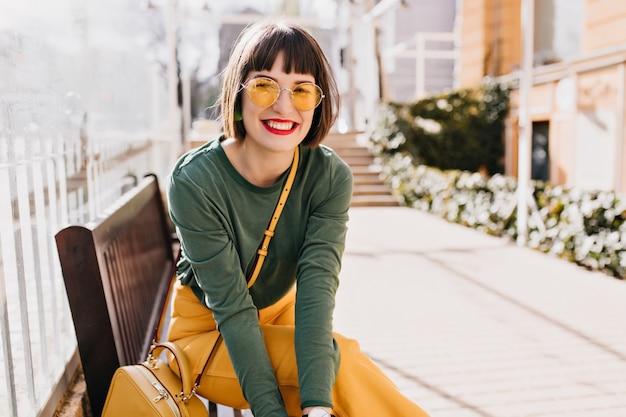 Смеющаяся элегантная женщина охлаждает после весенней прогулки. внешнее фото симпатичной дамы брюнет сидя на скамейке.