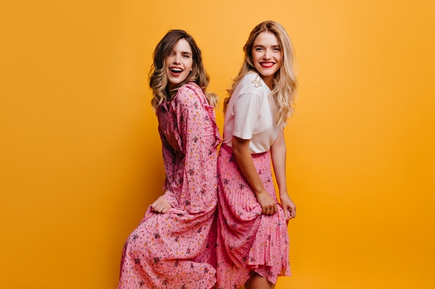 Laughing elegant woman in long dress enjoying photoshoot with sister. ecstatic blonde girl in white t-shirt spending time with best friend.
