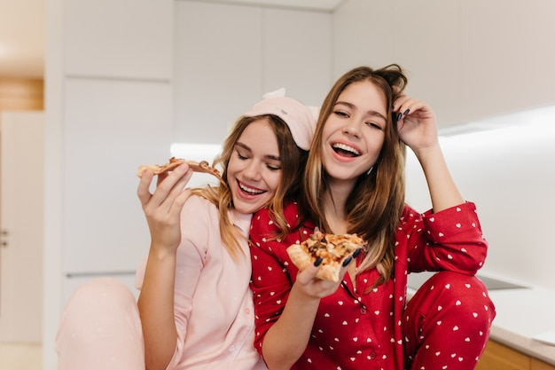 Laughing european woman in cute sleepwear spending morning with sister in eyemask. pretty white ladies eating cheese pizza with pleasure.
