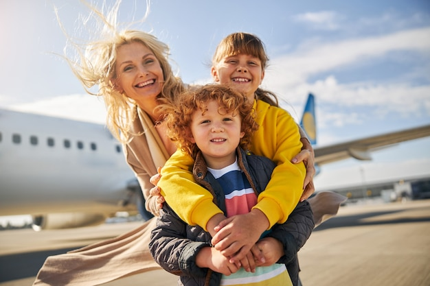 Laughing family is standing outside the plane
