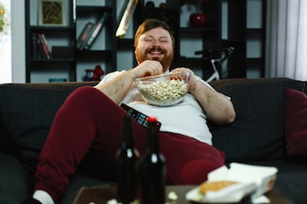 Laughing fat man sits on the sofa, eats pop-corn and watches TV