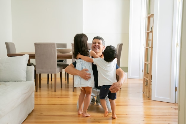 Laughing father hugging adorable little kids at home
