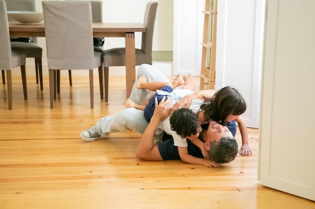 Laughing father lying on floor and hugging cute children.