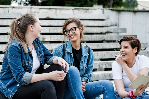 Laughing female friends sitting on stairs