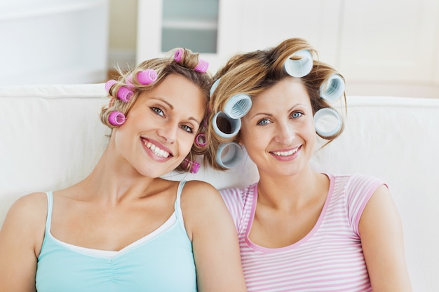 Laughing female friends with hair rollers on a sofa