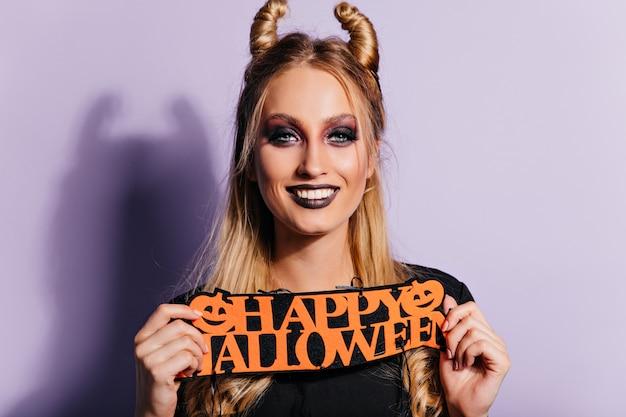 Смеющаяся женская модель с темным макияжем на хэллоуин позирует на фиолетовой стене. фото красивой блондинки в помещении.