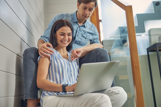 노트북을 사용하는 동안 집에서 쉬고있는 남자 친구와 함께 웃는 여성