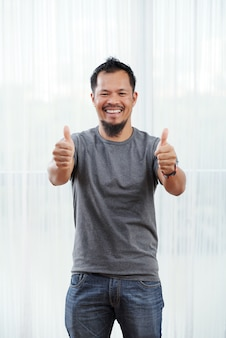 Laughing filipino man standing in front of brightly lit window with his thumbs up