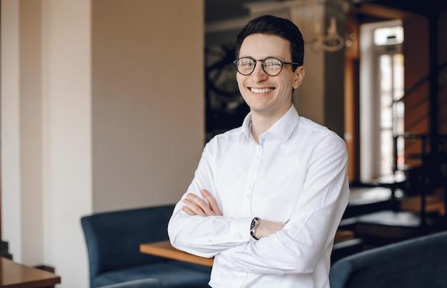 Смеющийся фрилансер позирует со скрещенными руками, глядя в очки, одетый в белую рубашку