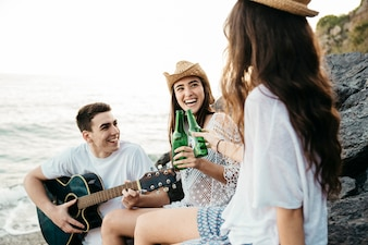 Laughing friends at the beach with guitar