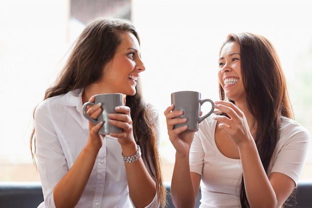 Смеющиеся друзья, имеющие кофе