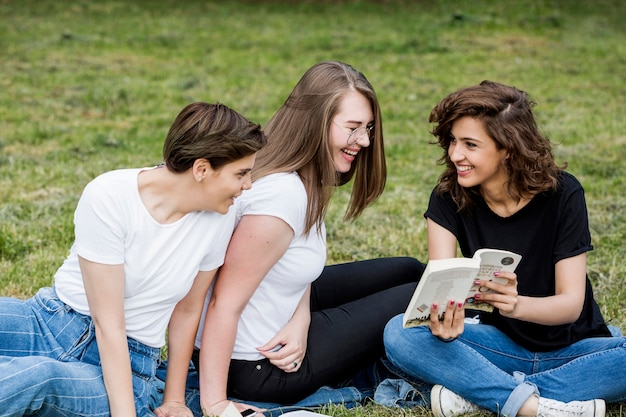 Laughing friends looking at book in park