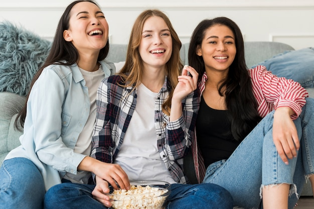 Laughing friends sharing bowl of popcorn