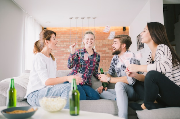 Laughing friends throwing with playing cards Free Photo
