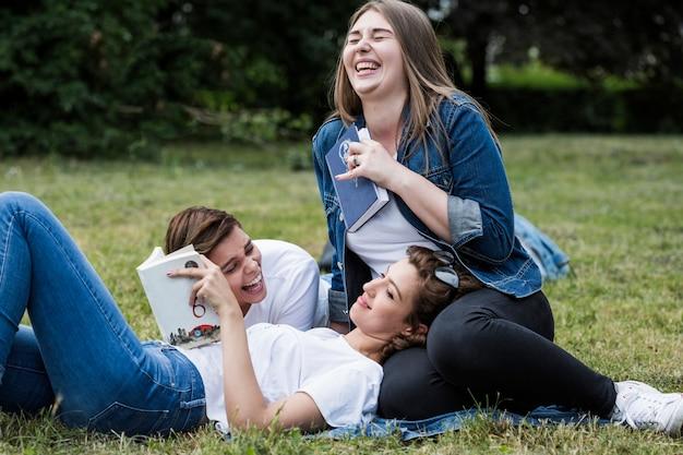 Смех друзей с книгами в парке Бесплатные Фотографии