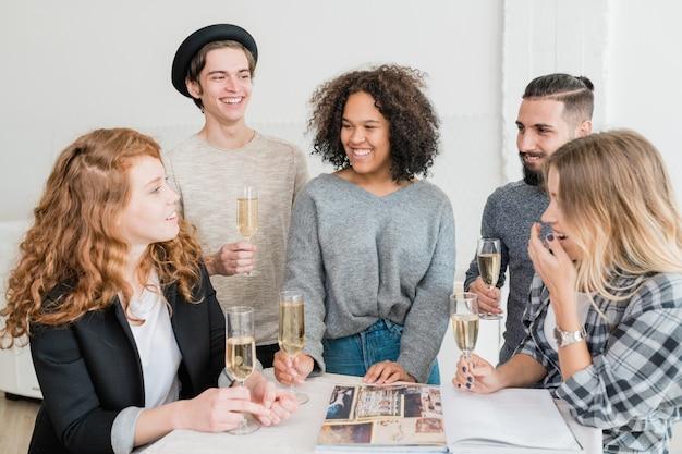 ホームパーティーのテーブルで面白いものを話している女の子の1人を見てシャンパンのフルートと友達を笑ってください。