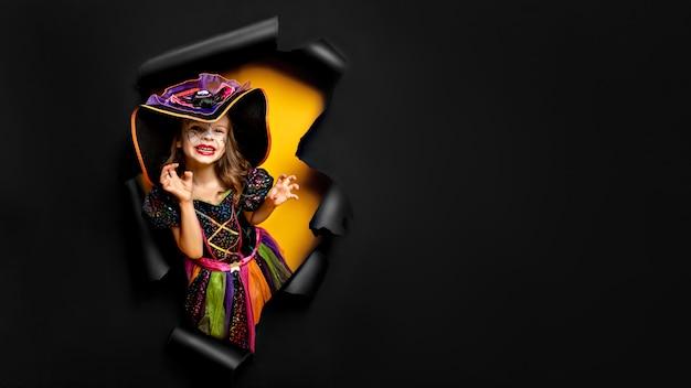 Смеющаяся смешная девочка в костюме ведьмы на хэллоуин смотрит, улыбается и пугает сквозь дыру на черно-желтом бумажном фоне