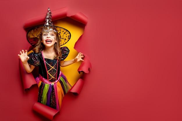 Смеющаяся смешная детская девочка в костюме ведьмы хэллоуина смотрит, улыбается и пугает сквозь дыру на красном, желтом бумажном фоне.