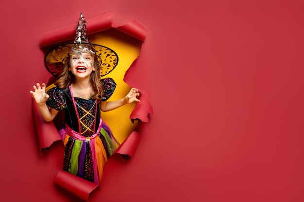 Laughing funny child girl in a witch costume of halloween looking, smiling and scares through a hole of red, yellow paper background.