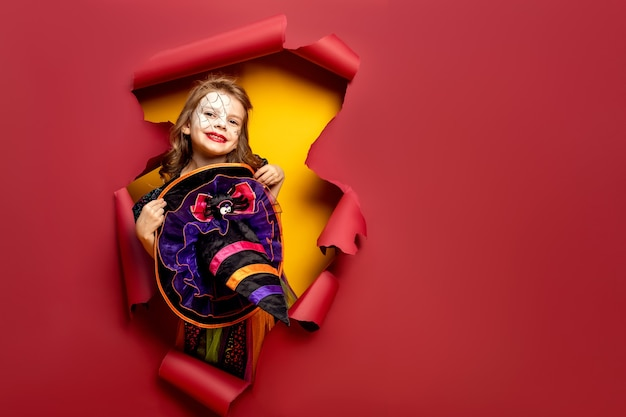 Laughing funny child girl in a witch costume of halloween looking through a hole of red and yellow paper background.