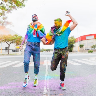Laughing gay couple running on road with rainbow flag