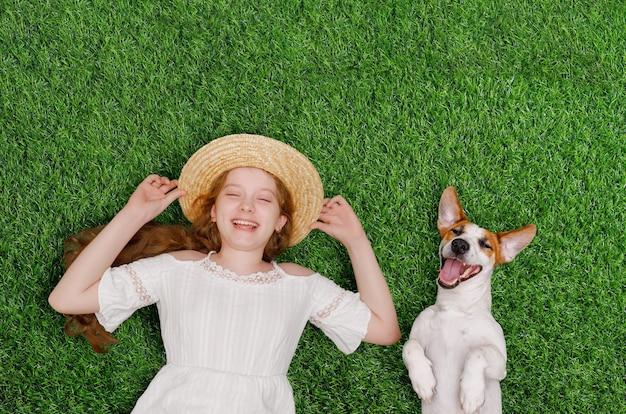 Смеющаяся девочка и милая собака наслаждаются летним днем на траве в парке