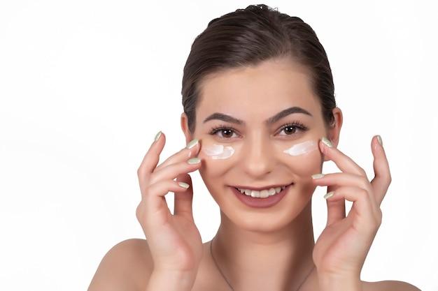 Смеющаяся девушка, применяя увлажняющий крем на лице. фото молодой девушки с безупречной кожей на белом фоне. концепция ухода за кожей и красоты