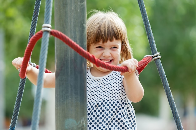 Laughing girl climbing at ropes