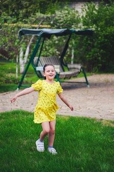 A laughing girl dances in a summer backyard with a garden swing in the background and enjoys a warm day