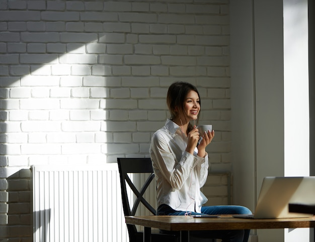 Laughing girl drinking coffee, working with laptop in the morning. wearing casual white shirt and blue jeans. sitting on wooden table, keepeng cup with coffee. feeling happy, satisfied.