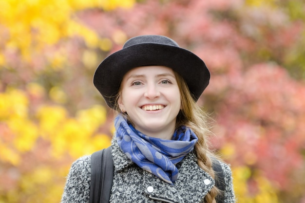 Laughing girl in a hat in autumn park. bright foliage on the background. portrait