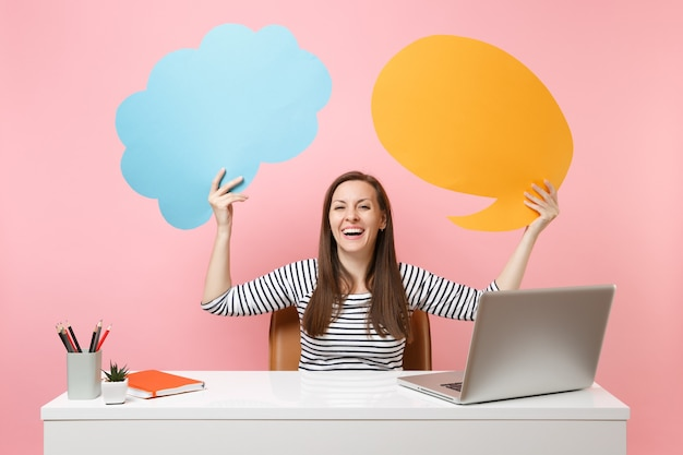 Laughing girl hold blue yellow empty blank say cloud speech bubble work at white desk with laptop isolated on pastel pink background. achievement business career concept. copy space for advertisement.