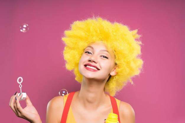 거품을 부는 분홍색 배경에 밝은 주황색 가발에 웃는 소녀