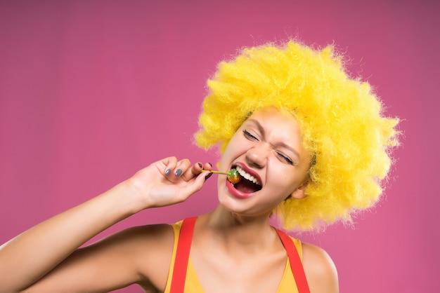 츄파 찹을 먹고 분홍색 배경에 밝은 주황색 가발에 웃는 소녀