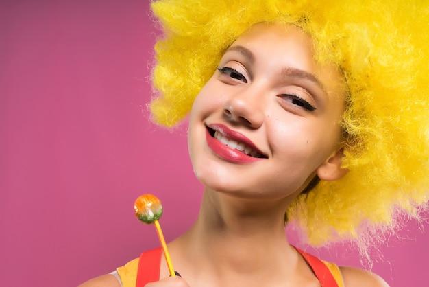 분홍색 배경에 밝은 주황색 가발을 쓴 웃는 소녀가 손에 츄파 찹을 들고 있다