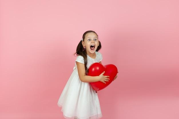 白いドレスを着た笑っている女の子は、半分横に立って、赤いハート型の風船を持っています