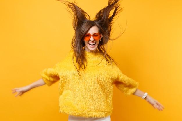 Смеющаяся девушка в оранжевых очках сердца мехового свитера дурачиться в студии прыгает с развевающимися волосами, изолированными на ярко-желтом фоне. люди искренние эмоции, концепция образа жизни. рекламная площадка.