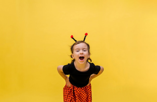Laughing girl in a ladybug costume on a yellow isolated