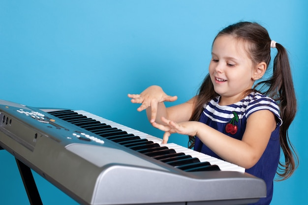 Laughing girl playing a melody on the keys of an electronic synthesizer