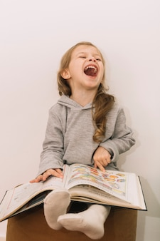 Laughing girl reading book on pouf