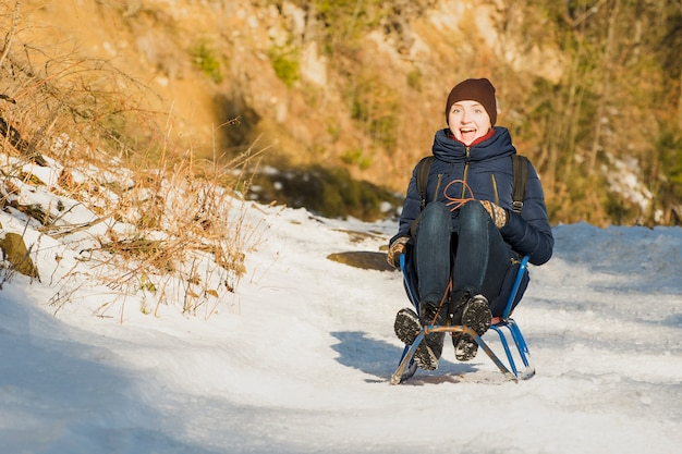 Laughing girl rides a small sled